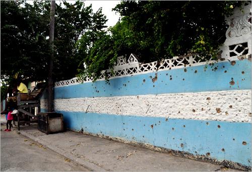 04. Un mur de Tivoli Gardens criblé d'impacts de balles.